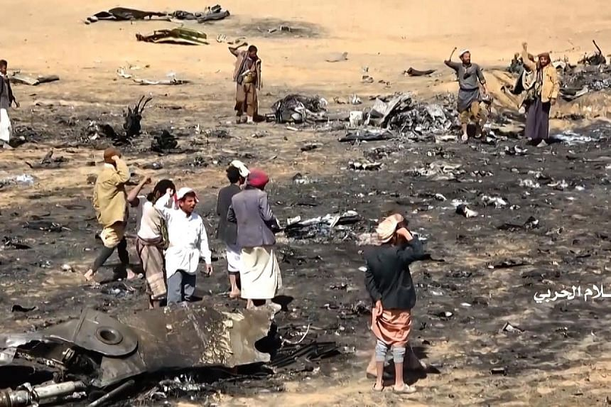 A screen grab from a video released by the Houthi Military Media Office on Saturday showing Yemenis gathering at the site of the downed Saudi Tornado aircraft in Yemen's northern Al-Jawf province.
