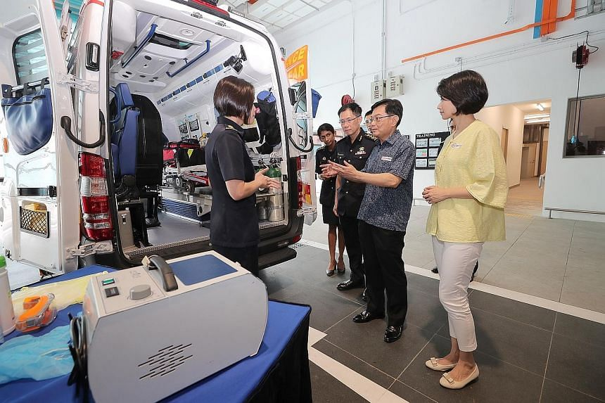 Deputy Prime Minister Heng Swee Keat and Senior Parliamentary Secretary for Home Affairs and National Development Sun Xueling being briefed on decontamination procedures by Singapore Civil Defence Force (SCDF) Lieutenant-Colonel Janice Oh (left) at K