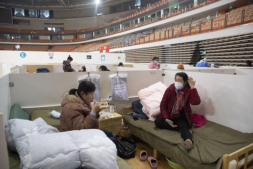 Patients at Wuhan Fangcang hospital, a makeshift hospital to treat coronavirus patients, in Wuhan city in China's Hubei province last Friday. The National Health Commission yesterday reported 2,009 new cases, down from 2,641 the previous day. PHOTO: