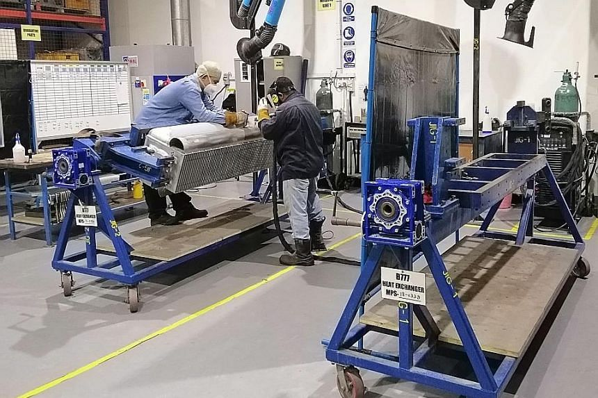 Workers welding on aircraft components at Coway Engineering's facility. The firm has invested more than $1 million over the past two years on initiatives to boost productivity, such as a vertical lean storage system that uses a carousel to transport