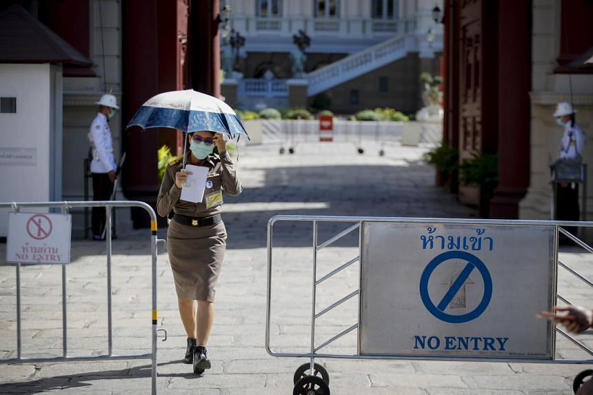 In a photo taken on Feb 14, 2020, a member of the Royal Thai police with a protective mask walks under an umbrella at the Grand Palace in Bangkok.
