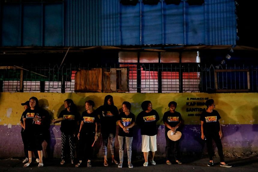 In a photo taken on Jan 27, 2020, members of a volunteer group of women take a break while patrolling with police officers on the streets of Pateros, Metro Manila, Philippines.