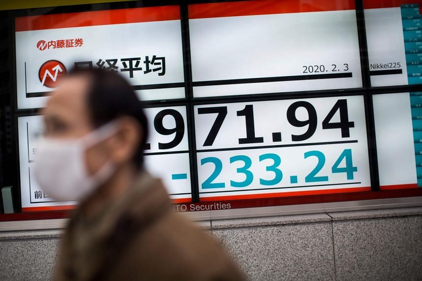 In a photo taken on Feb 5, 2020, a man with a face masks walks past a stock indicator displaying share prices of the Tokyo Stock Exchange in Tokyo.