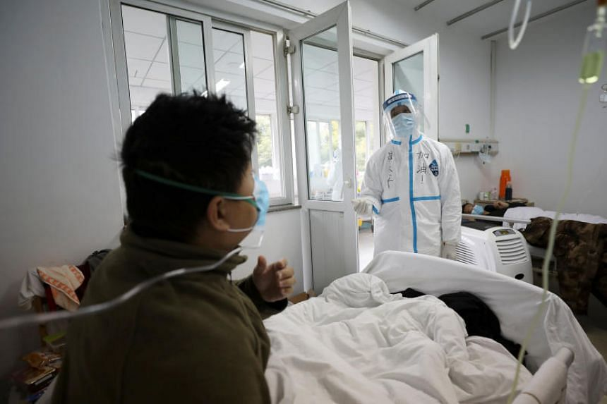 A medical worker in protective suit interacts with a patient inside an isolated ward at Jinyintan Hospital in Wuhan, China, on Feb 13, 2020.