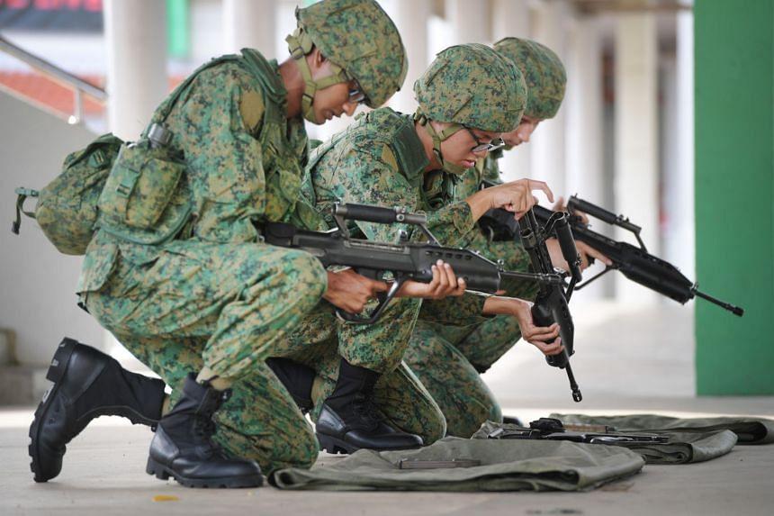 Recruits assemble SAR-21 rifles in Pulau Tekong on Feb 27, 2018.