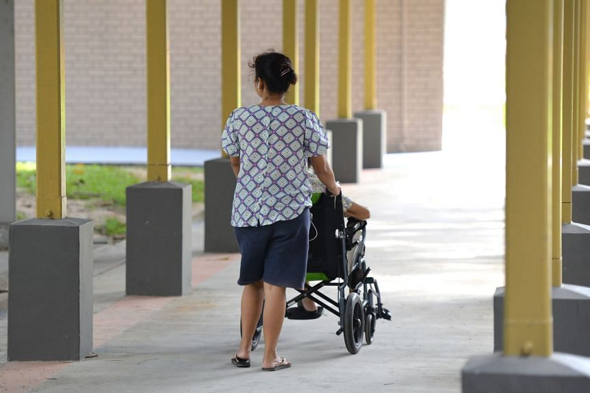 A domestic helper pushes an elderly woman in a wheelchair on Oct 25, 2019.