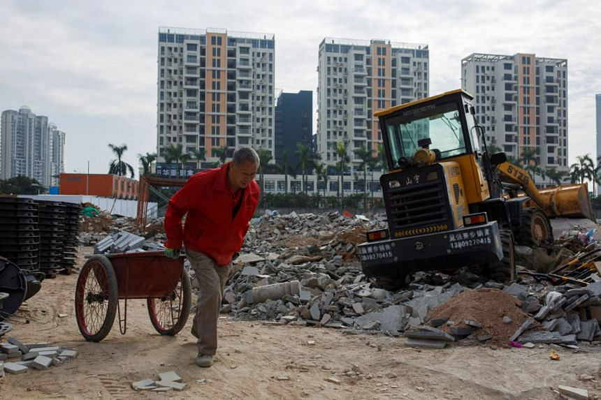 A worker pulls a cart at a construction site near new apartment high-rise buildings in the Shekou area of Shenzhen, Guangdong Province, China.