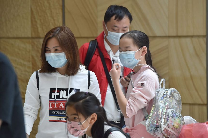 In a photo taken on Jan 23, 2020, a family arrives at Sydney airport after landing on a plane from the Chinese city of Wuhan.
