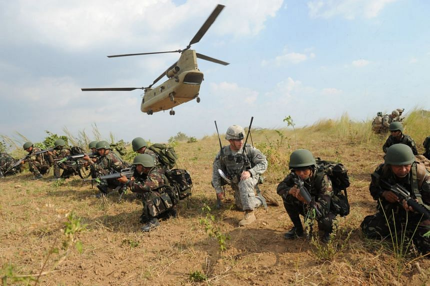In a photo taken on April 20, 2015, Philippine soldiers and a US Army soldier take their positions during an air assault exercise inside the military training camp in Nueva Ecija province.