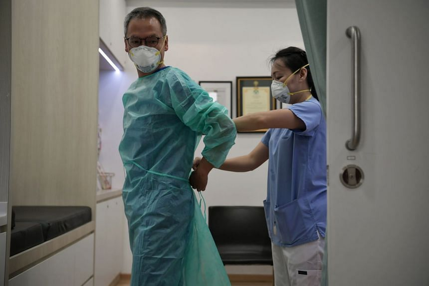 A doctor gets help from a triage nurse to don full protective equipment on Feb 13, 2020.