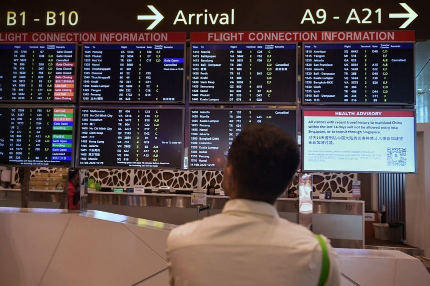 A man looks at the Arrivals flight schedule board at Changi Airport Terminal 3 on Feb 14, 2020.