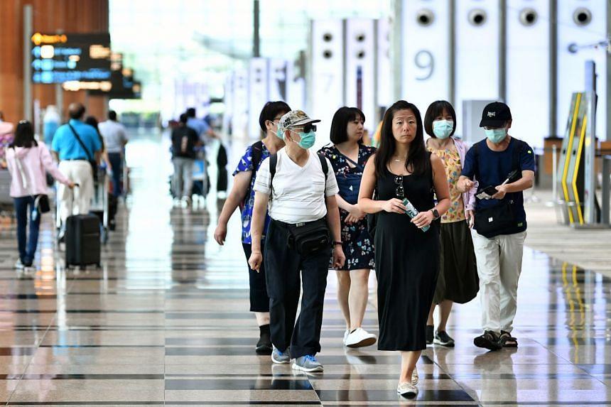 Visitors wearing face masks walk at Changi Airport Terminal 3 Departure Hall on Feb 12, 2020.