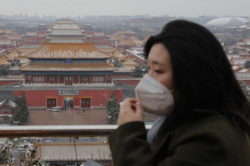 A woman wears a protective mask at Jingshan Park in Beijing on Feb 14, 2020.