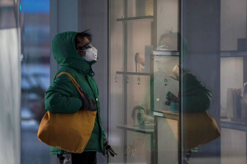In a photo taken on FEb 16, 2020, a woman wearing a face mask looks at a shopping window in Beijing's central business district.
