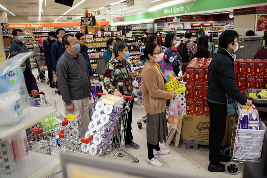 In a photo taken on Jan 7, 2020, shoppers with face masks  stock up on toilet paper rolls at a supermarket in Hong Kong.