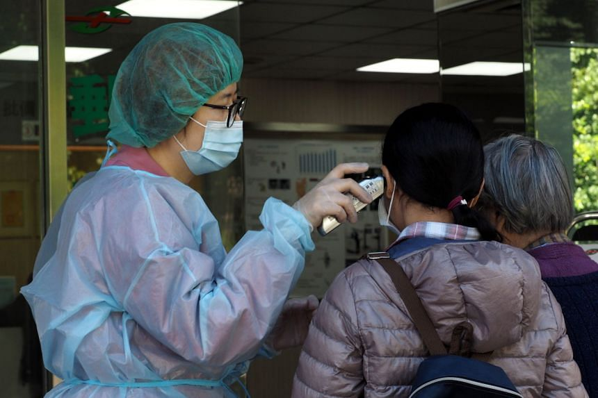 In a photo taken on Feb 6, 2020, a medical worker checks the temperature of a woman at a hospital's entrance in Taipei.
