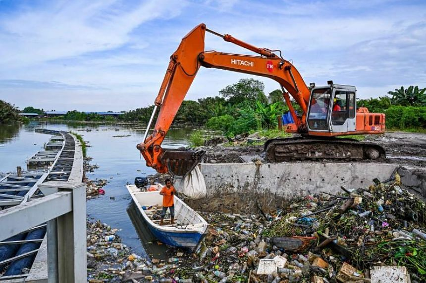 Workers clear mounds of floating plastic waste from the Klang river, on the outskirts of Kuala Lumpur, on Dec 17, 2019.