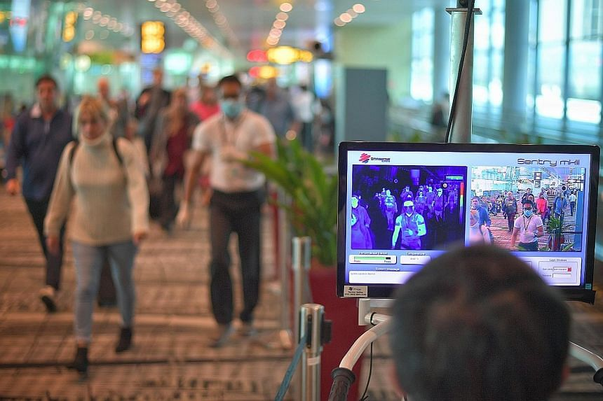 Temperature screening at the arrival area of Changi Airport Terminal 3. The new stay-home notice was prompted by the surge in the number of cases in China outside of Hubei. ST PHOTO: ARIFFIN JAMAR