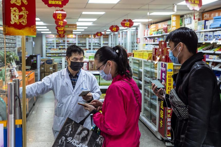 People form a queue in a pharmacy in Guangzhou, Guangdong, on Feb 11, 2020.