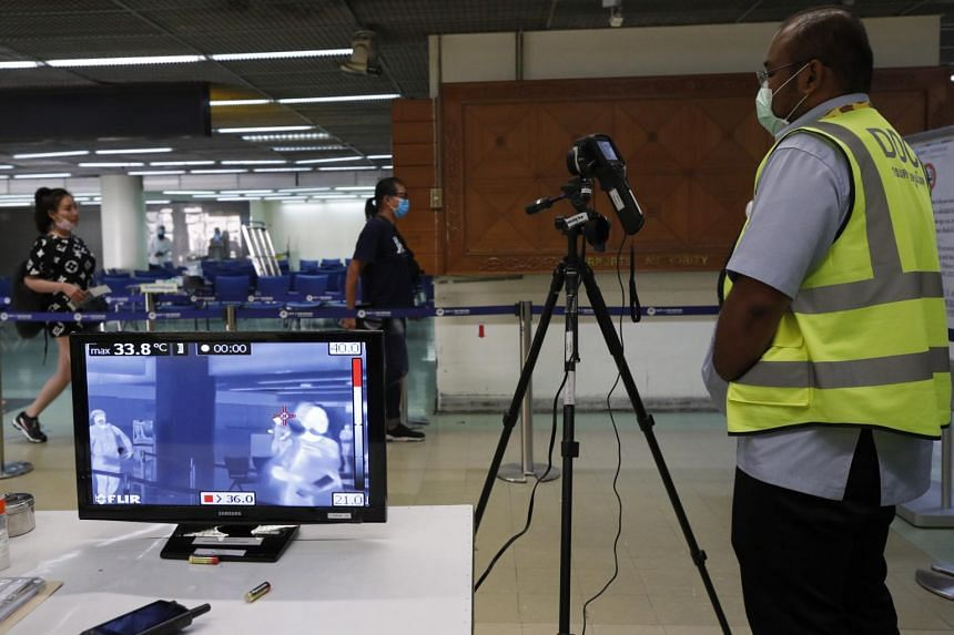 Thai health officials monitor arriving passengers from international flights with a thermal scan device at Don Mueang Airport in Bangkok, Thailand, on Feb 7, 2020.