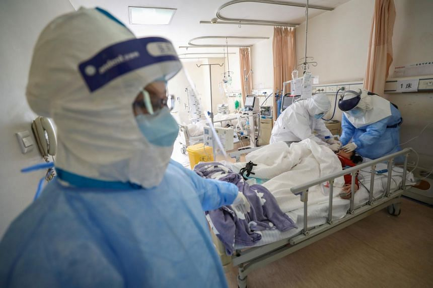 Medical workers in protective suits attend to a patient inside an isolation ward of Wuhan Red Cross Hospital in Wuhan on Feb 16, 2020.