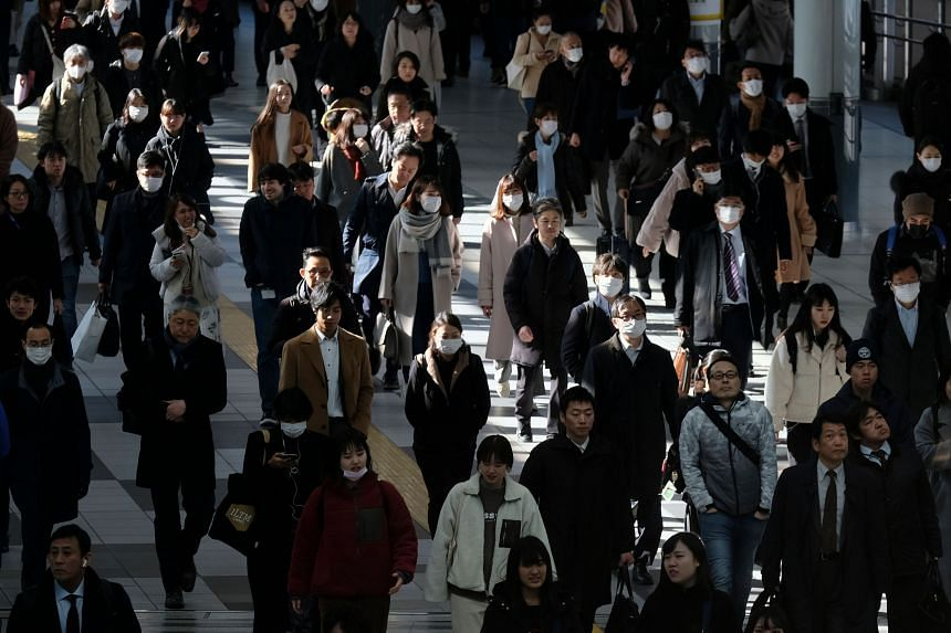 In a photo taken on Jan 31, 2020, commuters walk on a concourse at a railway's terminal station in Tokyo.