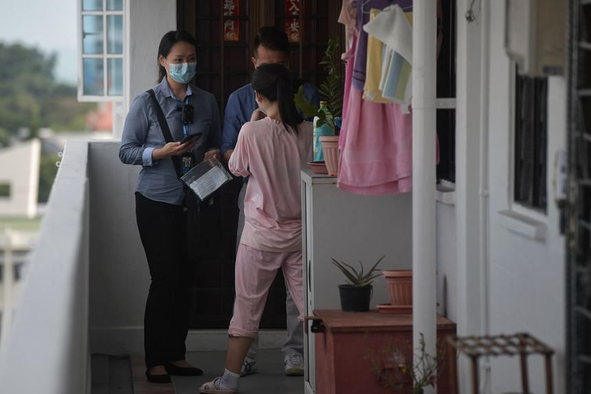 In a photo from Feb 12, 2020, enforcement officers check on a work pass holder who is nearing the end of her mandatory leave of absence in Bedok.
