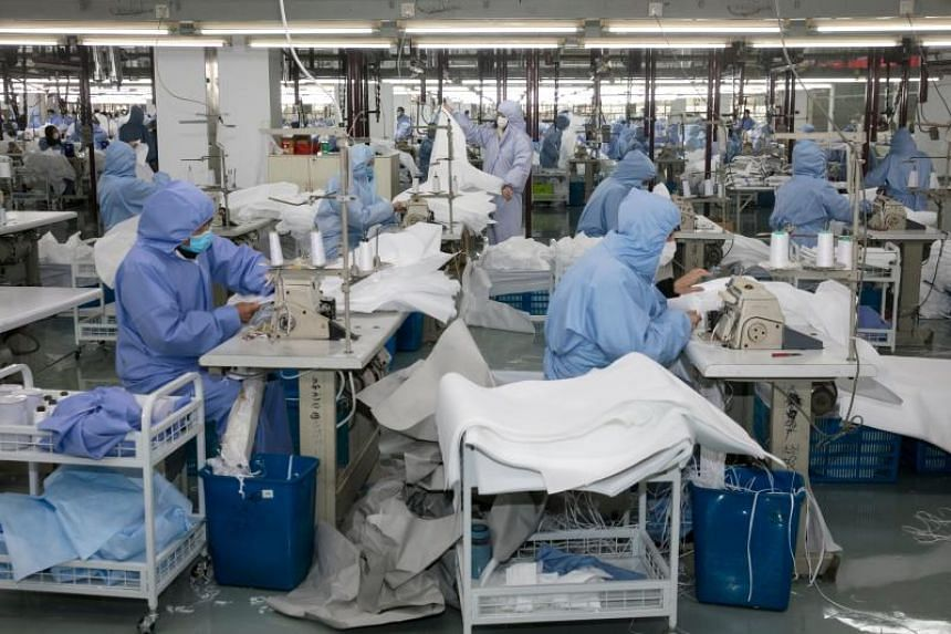 Workers producing protective clothing at a factory in Wuxi, China, on Feb 8. 2020.