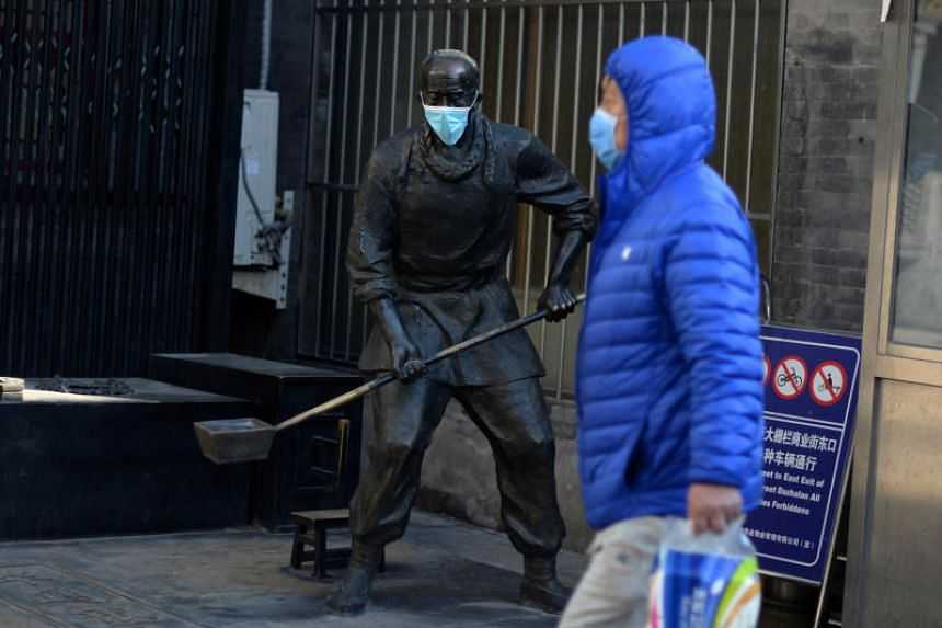 A man wearing a face mask walks past a statue with a face mask on near the Qianmen pedestrian street in Beijing, China, on Feb 18, 2020.