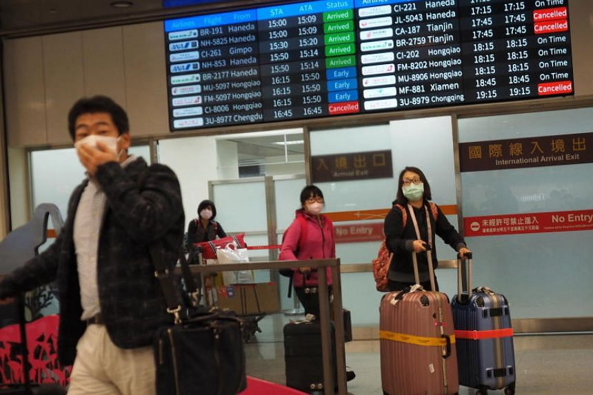 Passenges wearing face masks arrive at Taipei Songshan Airport in Taipei, Taiwan on Feb 16, 2020.