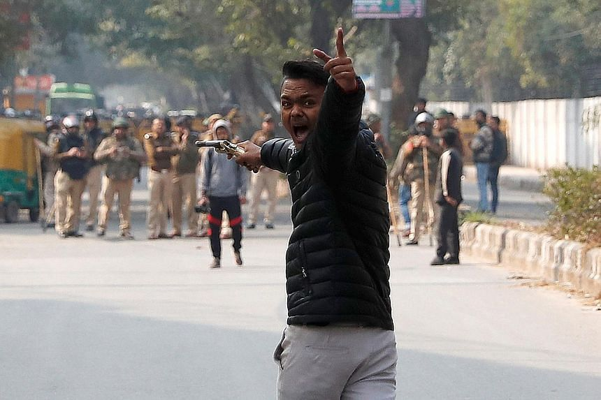 An unidentified teenager brandishing a gun during a protest on Jan 30 against a new citizenship law outside the Jamia Millia Islamia university in New Delhi, India.
