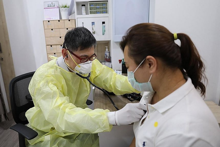 An employee at a Northeast Medical Group clinic, one of hundreds designated as a Public Health Preparedness Clinic, receiving medical supplies such as N95 and surgical masks yesterday. The Health Ministry sent out two weeks' worth of personal protect