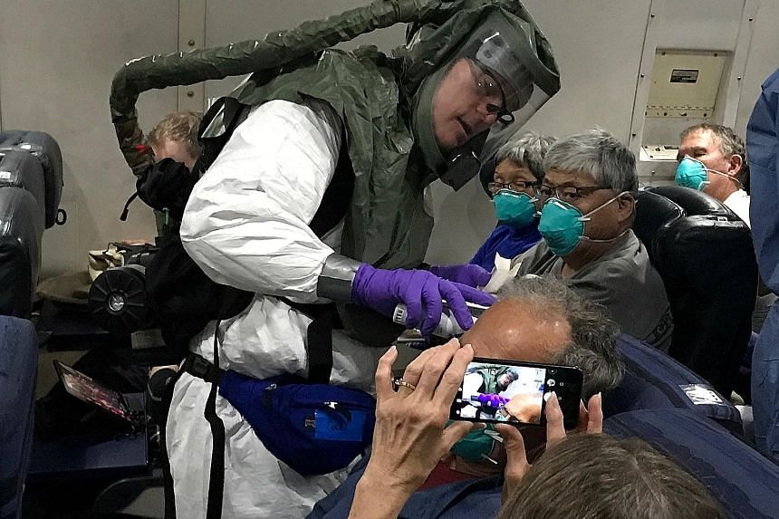 A worker in a protective suit checking the temperatures of passengers who were on board the Diamond Princess cruise ship, on a chartered evacuation aircraft from Tokyo's Haneda Airport, en route to Lackland Air Force Base in the US on Monday.