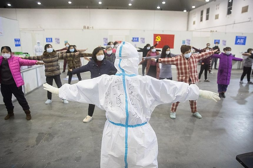 Patients exercising with medical staff inside the Wuhan Fang Cang makeshift hospital in Wuhan on Monday.