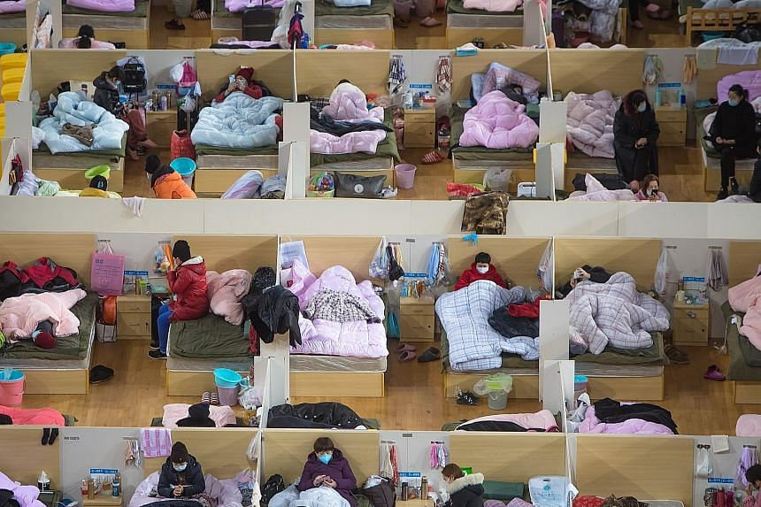 Patients in a temporary hospital in Wuhan, which was converted from Wuhan Sports Centre, on Monday. The authorities throughout China have implemented various curbs on travel and movement to contain the outbreak, which has killed 1,868 people in mainl