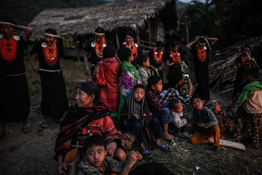 A photo taken on Feb 7, 2020, shows villagers watching the end of an overnight ceremony to bless the harvest by Naga tribeswomen in Satpalaw Shaung village, Lahe township in Myanmar's Sagaing region.