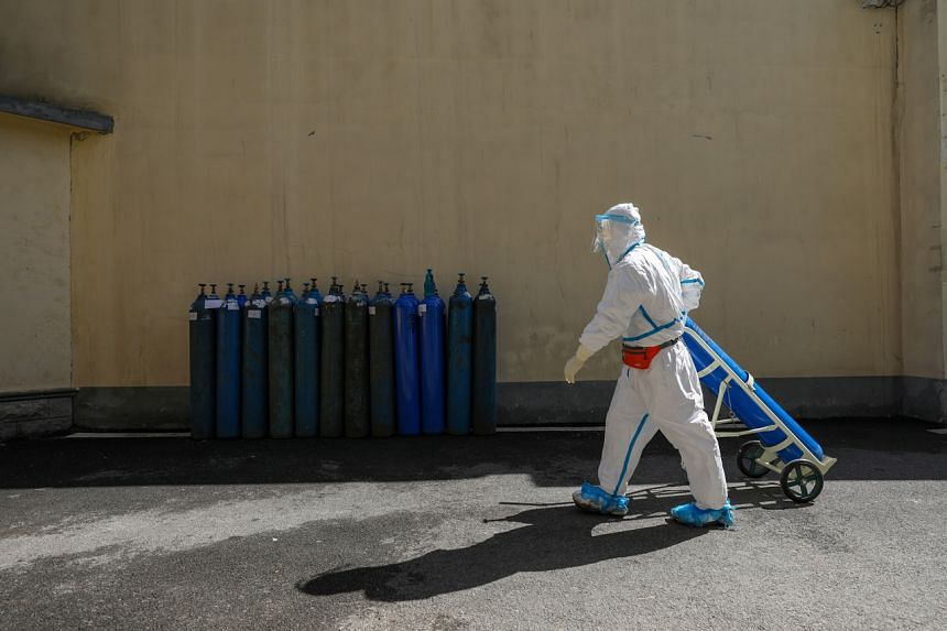 A medical worker in protective suit transporting an oxygen tank at the Wuhan Red Cross Hospital in China on Feb 16, 2020.