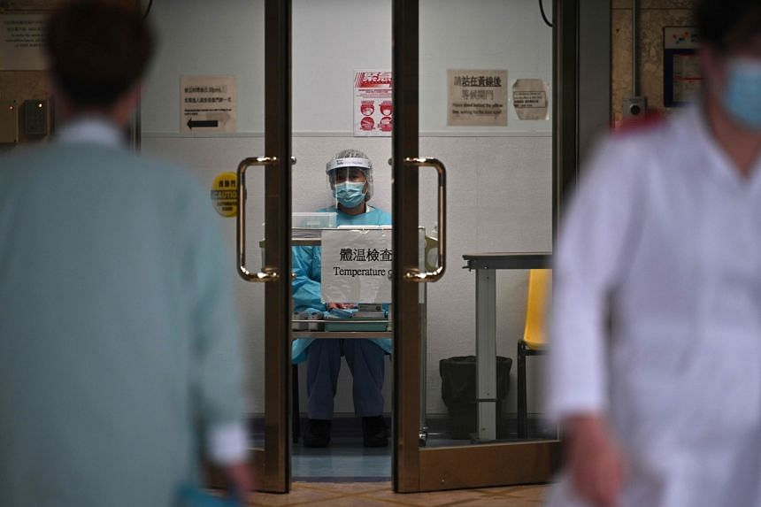 A medical worker wearing protective gear (centre) waits to take the temperature of people at an entrance of Princess Margaret Hospital in Hong Kong on Feb 4, 2020.