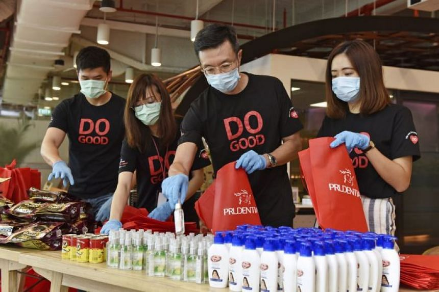 Prudential Singapore's chief customer officer Goh Theng Kiat (second from right) with the insurer's employees preparing care kits to be distributed to 1,000 seniors as part of support efforts for the Ang Mo Kio Family Services Centre.