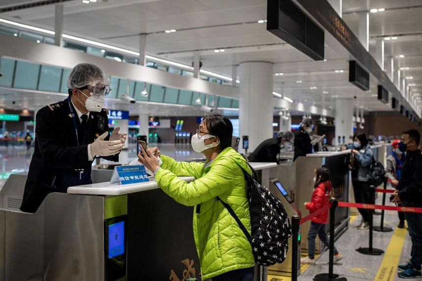 A health quarantine officer checking the health documents of a passenger at Daxing international airport in Beijing on Feb 14, 2020.