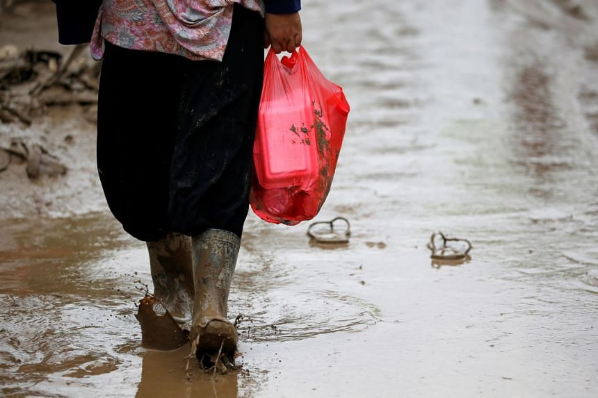 A woman carrying a plastic bag containing food in Bekasi, West Java province, Indonesia, on Jan 3, 2020.