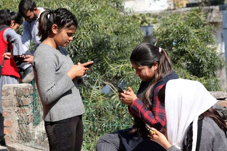 Indian students trying to connect their mobile phone to a VPN to access social media after the government blocked VPNs in Jammu and Kashmir State.