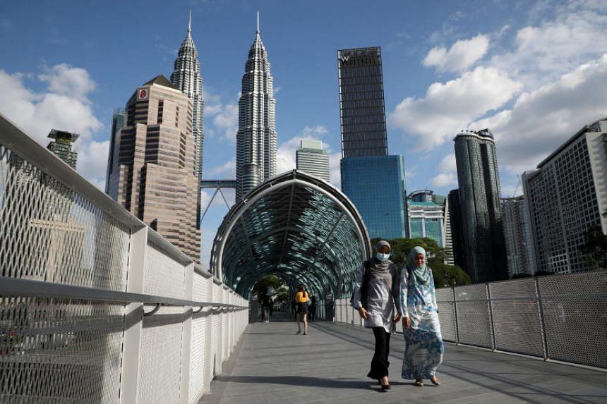 A woman wearing a protective face mask crosses a bridge in Kuala Lumpur, on Feb 19, 2020.