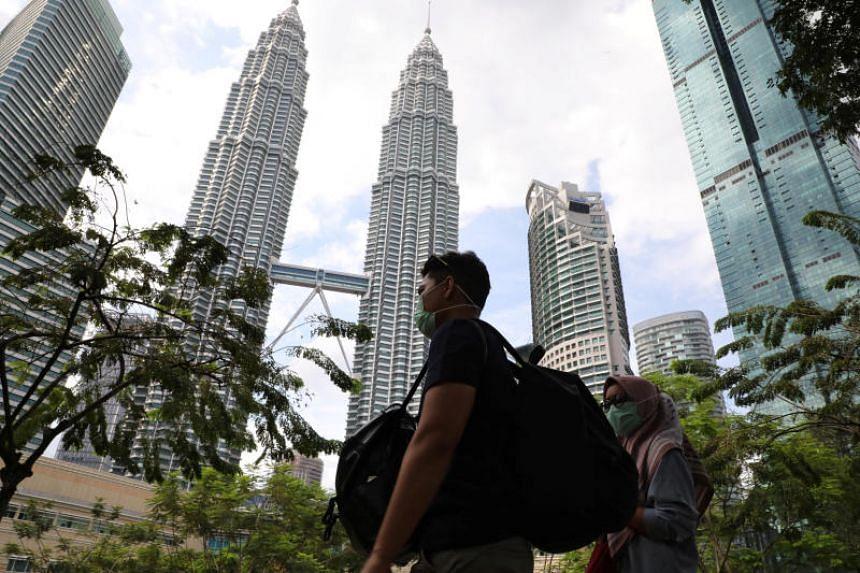 Tourists wearing masks pass by the Petronas Twin Towers in Kuala Lumpur, Malaysia, on Jan 31, 2020.