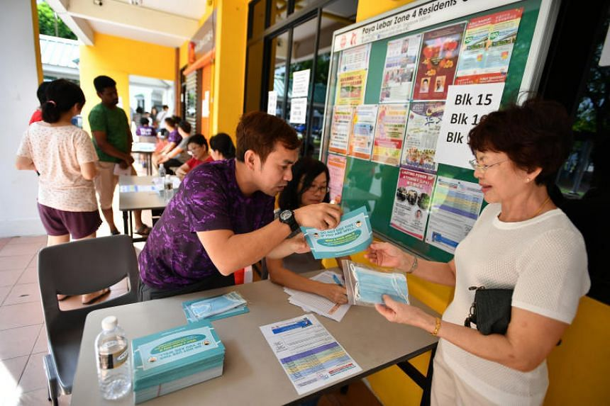 A member of the public collecting her face masks in Hougang on Feb 1, 2020.