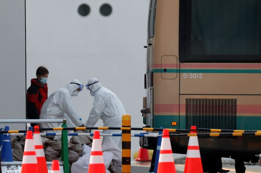 Workers in protective gear help to load disembarking passengers luggage onto a bus after leaving the Diamond Princess cruise ship docked at Yokohama Port, south of Tokyo, Japan, on Feb 20, 2020.