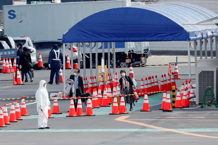A passenger disembarks from the Diamond Princess cruise ship at the Daikoku Pier Cruise Terminal in Yokohama on Feb 19, 2020.