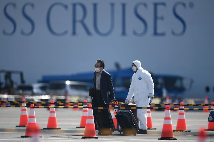 A passenger (left) disembarks from the Diamond Princess cruise ship at the Daikoku Pier Cruise Terminal in Yokohama, on Feb 19, 2020.