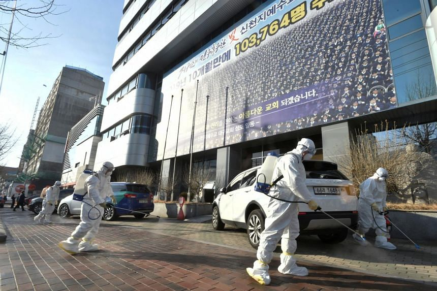 Workers from a disinfection service company sanitise a street in front of a branch of the Temple of the Tabernacle of the Testimony in Daegu, South Korea, on Feb 19, 2020.