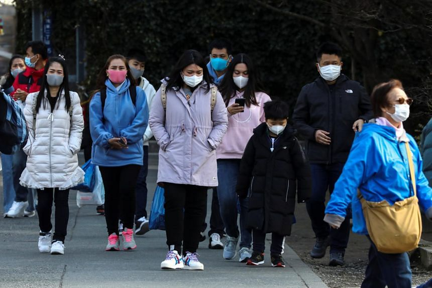 Tourists wearing protective masks visit Sensoji Temple in Asakusa district in Tokyo, Japan, on Feb 18, 2020.